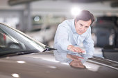 Mid adult man looking at car bonnet in showroom