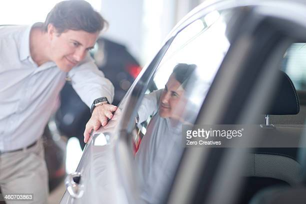 Mid adult man looking at car in showroom