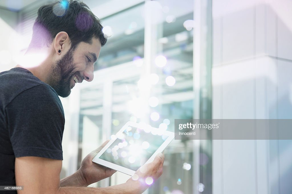 Mid adult man looking at lights coming from digital tablet : Stock Photo