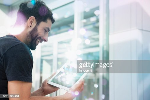 Mid adult man looking at lights coming from digital tablet