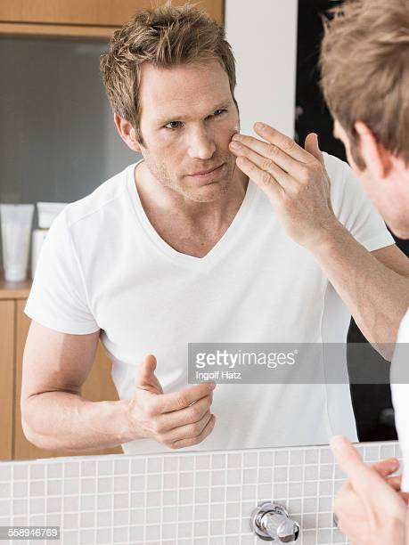 Mid adult man looking in bathroom mirror applying face cream