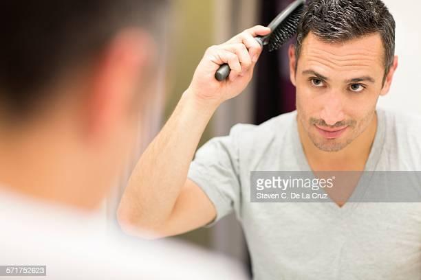 Mid adult man, looking in mirror, brushing hair