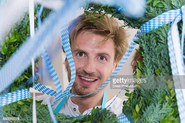 Mid adult man looking through wreath, smiling