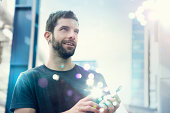 Mid adult man looking up at lights coming from smartphone
