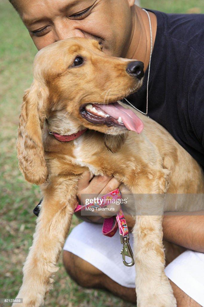 Mid adult man loving a dog : Stock Photo
