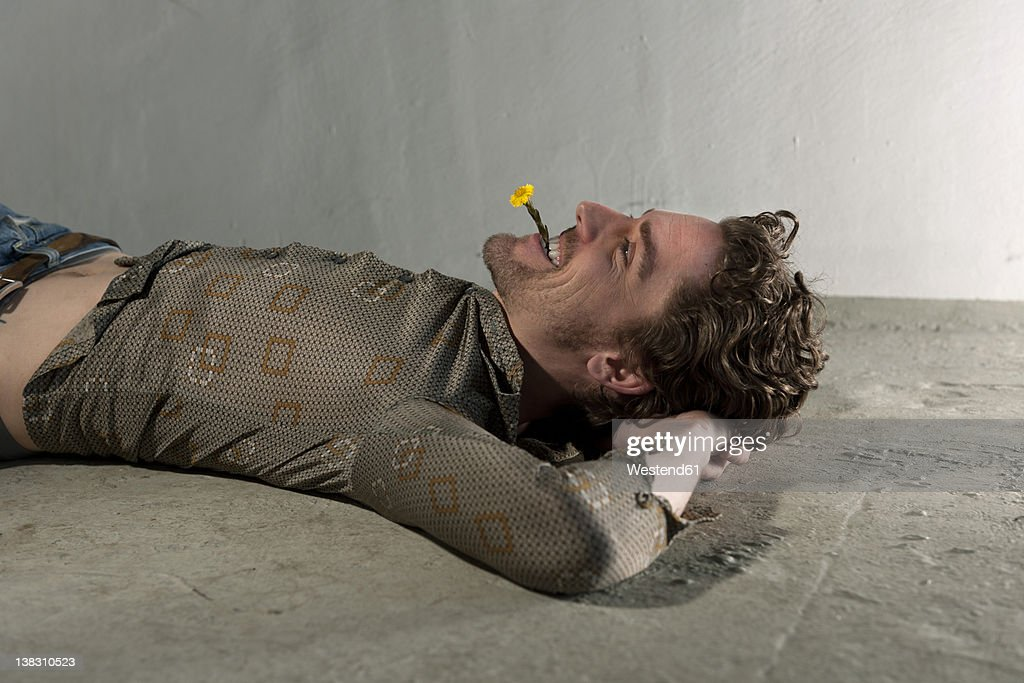 Mid adult man lying on floor and holding flower in mouth
