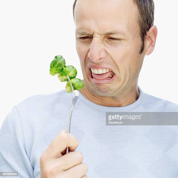 mid adult man making a face in front of a fork with Brussels sprouts