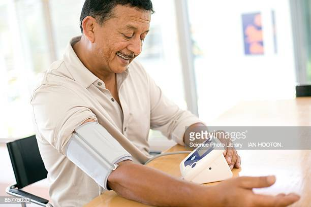 Mid adult man measuring blood pressure