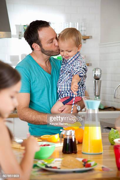 Mid adult man multi tasking breakfast with son and daughter