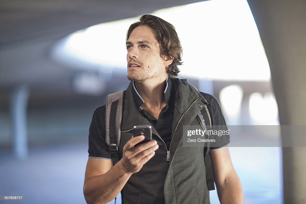 Mid adult man navigating with smartphone in city