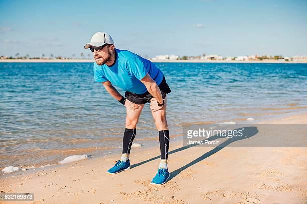 Mid adult man on coastline bending forwards looking away, Dubai, United Arab Emirates