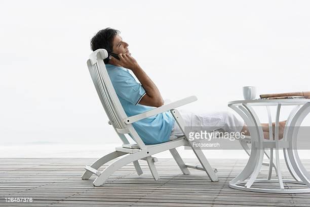 Mid adult man on phone near beach