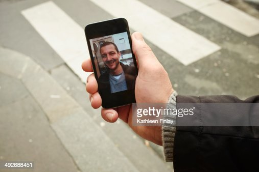 Mid adult man on sidewalk holding smartphone with photograph on screen
