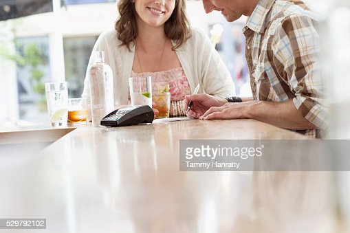Mid adult man paying bill in bar : Stock Photo