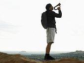 Mid adult man playing bugle on rock