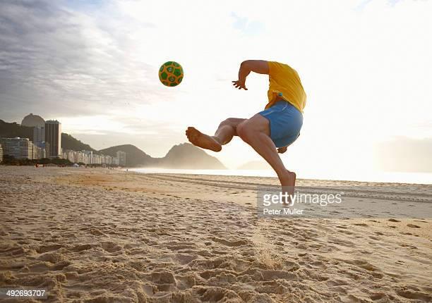 Mid adult man playing soccer on Copacabana beach, Rio De Janeiro, Brazil