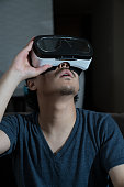 Mid adult man playing with a virtual reality headset