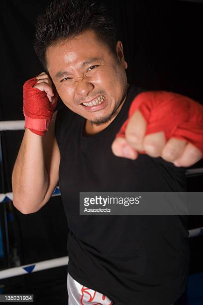 Mid adult man practicing boxing in a boxing ring