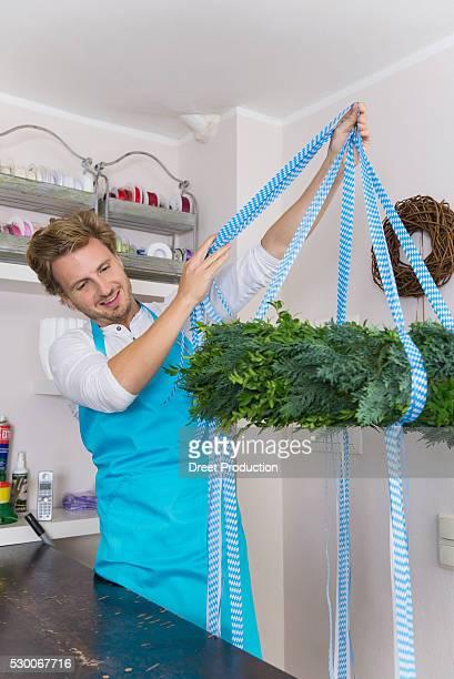 Mid adult man preparing floral wreath in flower shop