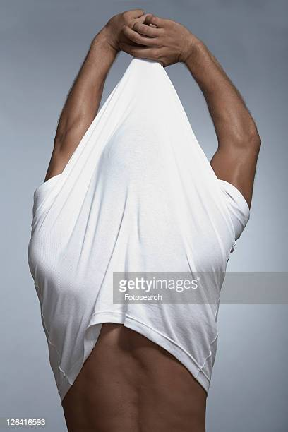 Mid adult man pulling T-shirt off
