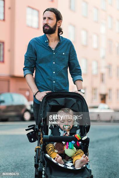Mid adult man pushing baby in carriage on sidewalk