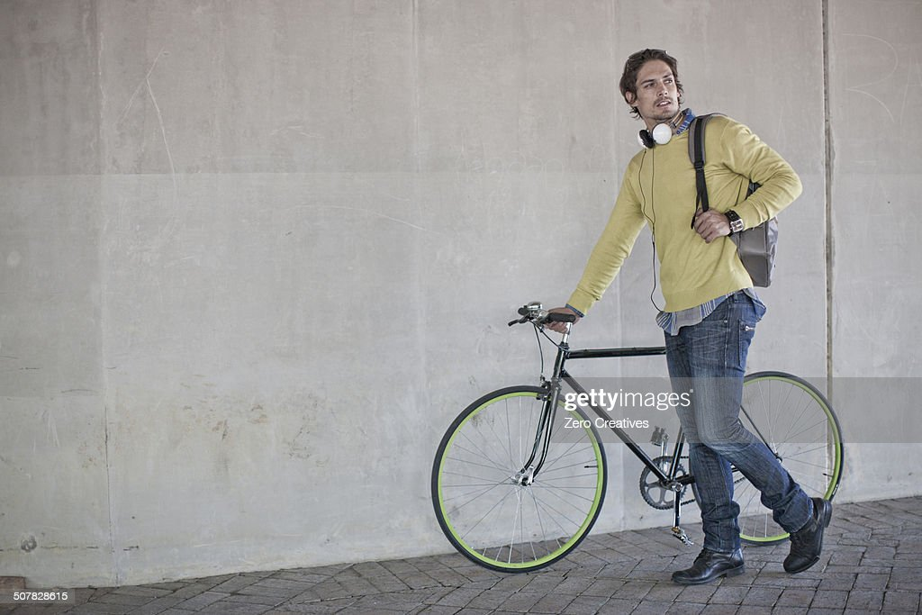 Mid adult man pushing bicycle through city underpass