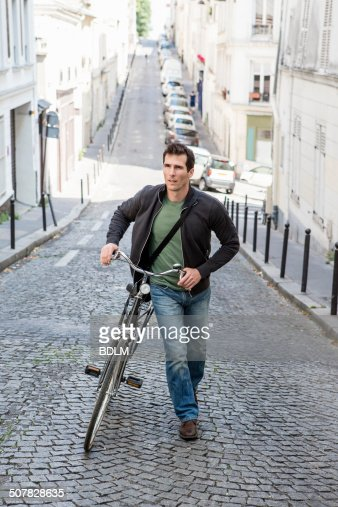 Mid adult man pushing bicycle up cobbled city street