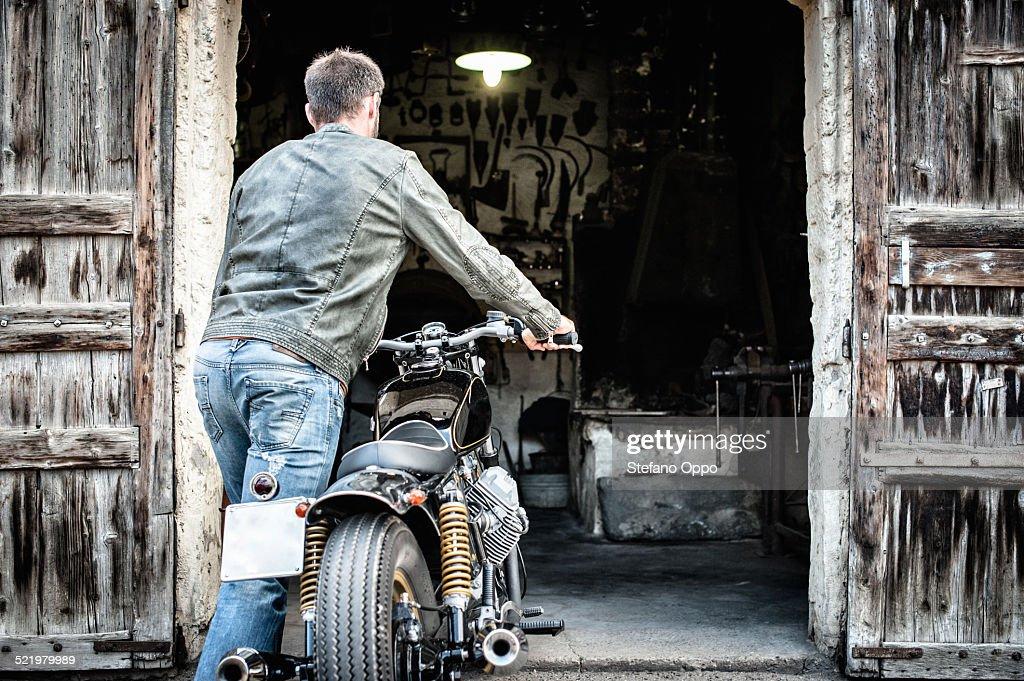 Mid adult man pushing motorcycle into barn