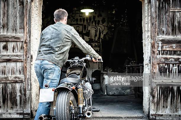 Mid adult man pushing motorcycle into barn