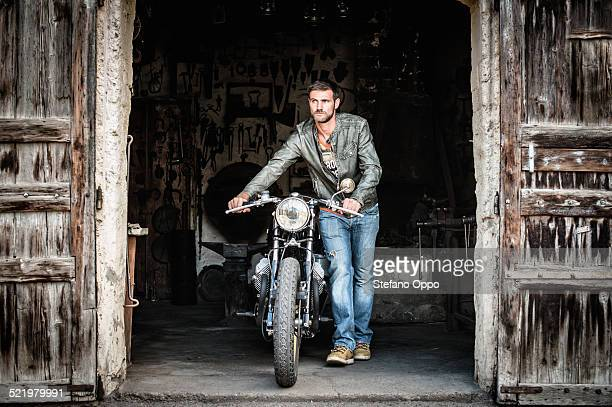 Mid adult man pushing motorcycle out of barn doorway