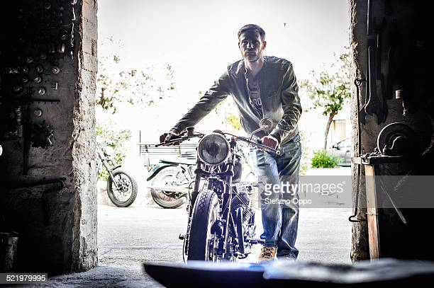 Mid adult man pushing motorcycle through barn doorway