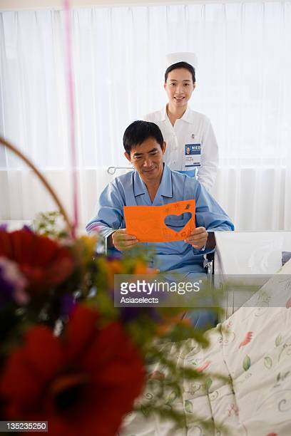 Mid adult man reading a Get Well card with a female nurse standing behind him