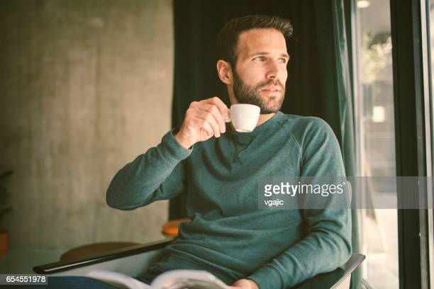 Mid Adult man reading book in cafe