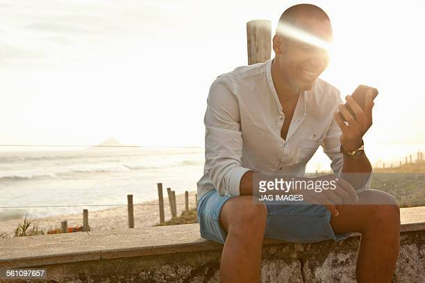 Mid adult man reading smartphone texts at beach, Rio De Janeiro, Brazil
