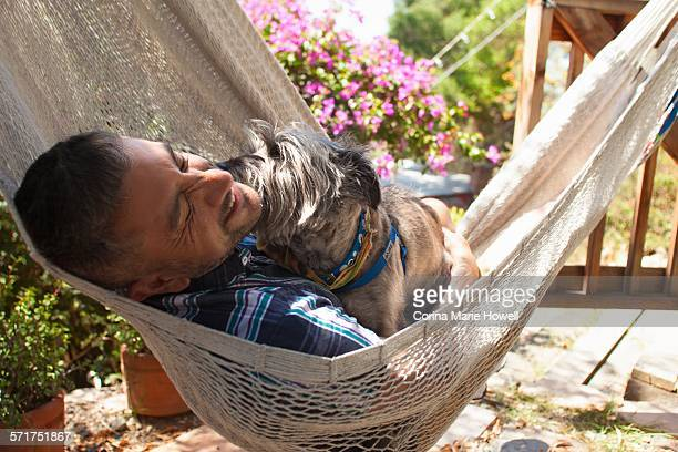 Mid adult man reclining in garden hammock with dog