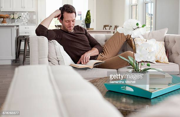 Mid adult man relaxing at home on sofa, reading book