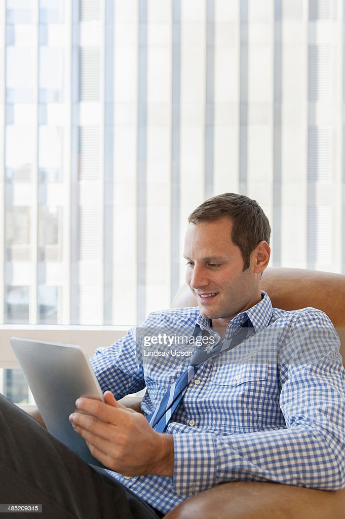 Mid adult man relaxing at home with digital tablet : Stock Photo