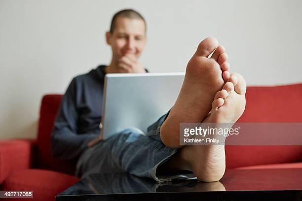 Mid adult man relaxing on sofa engrossed in laptop