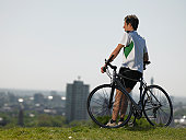 Mid adult man resting on hill after bike ride, city in background