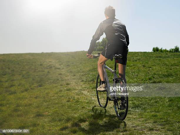 Mid adult man riding bicycle uphill, rear view