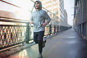 Mid adult man running across bridge