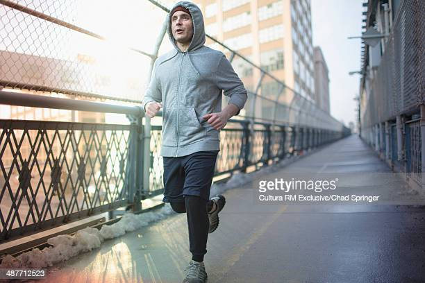 Mid adult man running across bridge