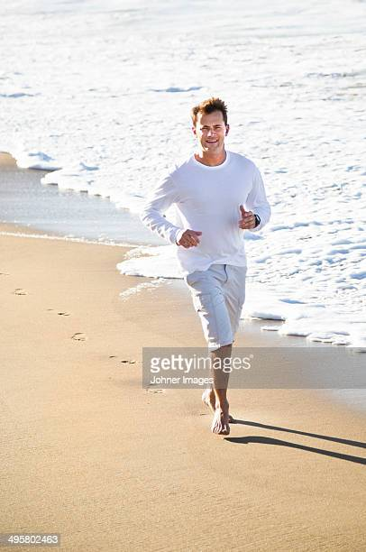 Mid adult man running on beach