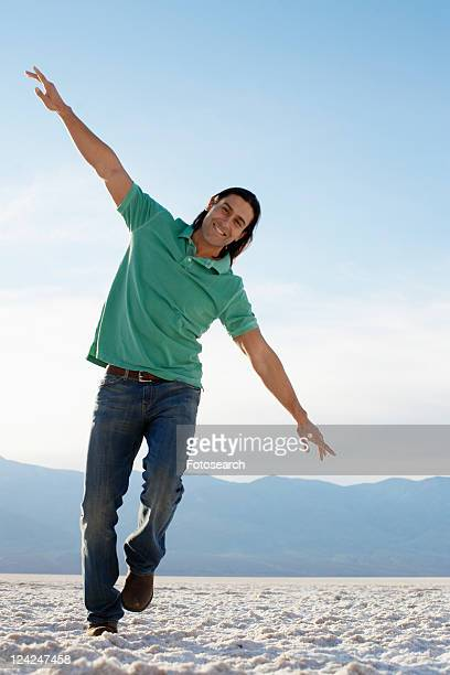 Mid adult man running with arms outstretched in desert