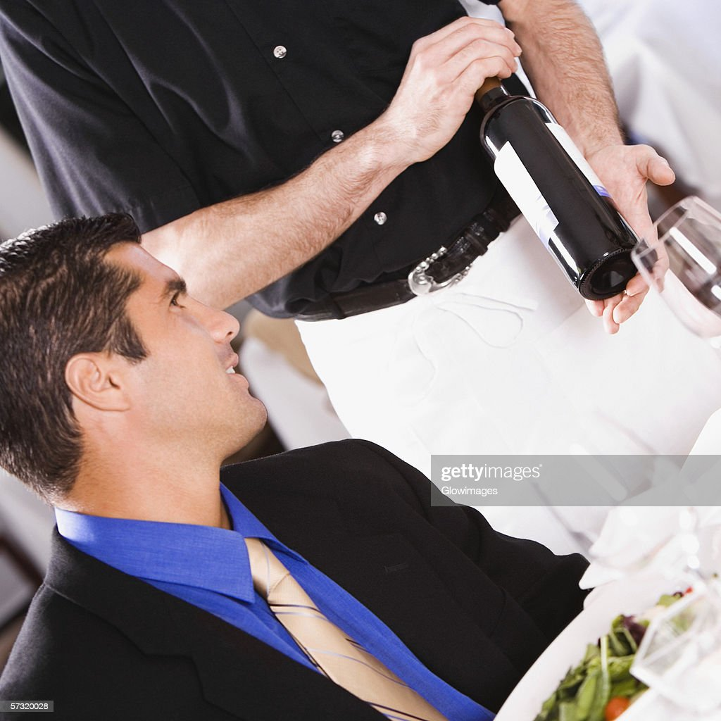 Mid adult man sitting at a table with a waiter standing beside him : Stock Photo