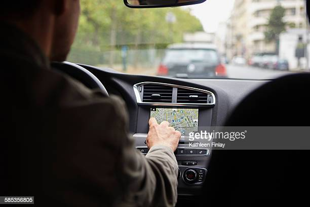 Mid adult man sitting in car, using gps