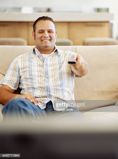 mid adult man sitting in front of a television using a remote control