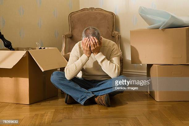 Mid adult man sitting on a hardwood floor and suffering from a headache