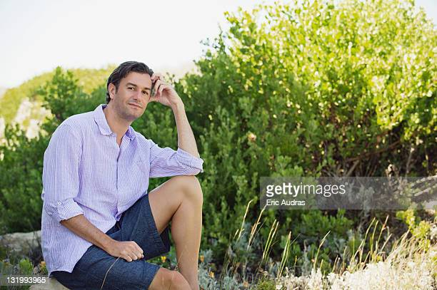 Mid adult man sitting on a rock in a garden and thinking