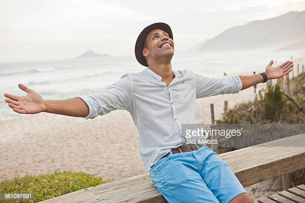 Mid adult man sitting on boardwalk fence with arms open, Rio De Janeiro, Brazil